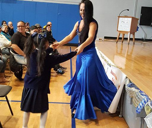 Flamenco Dancer dances with a student volunteer in front of stage with parents looking on.