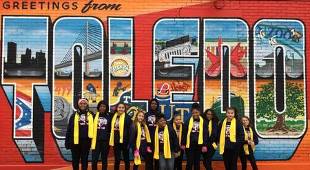 Picture of students of National School Choice dance team standing in front of Toledo mural
