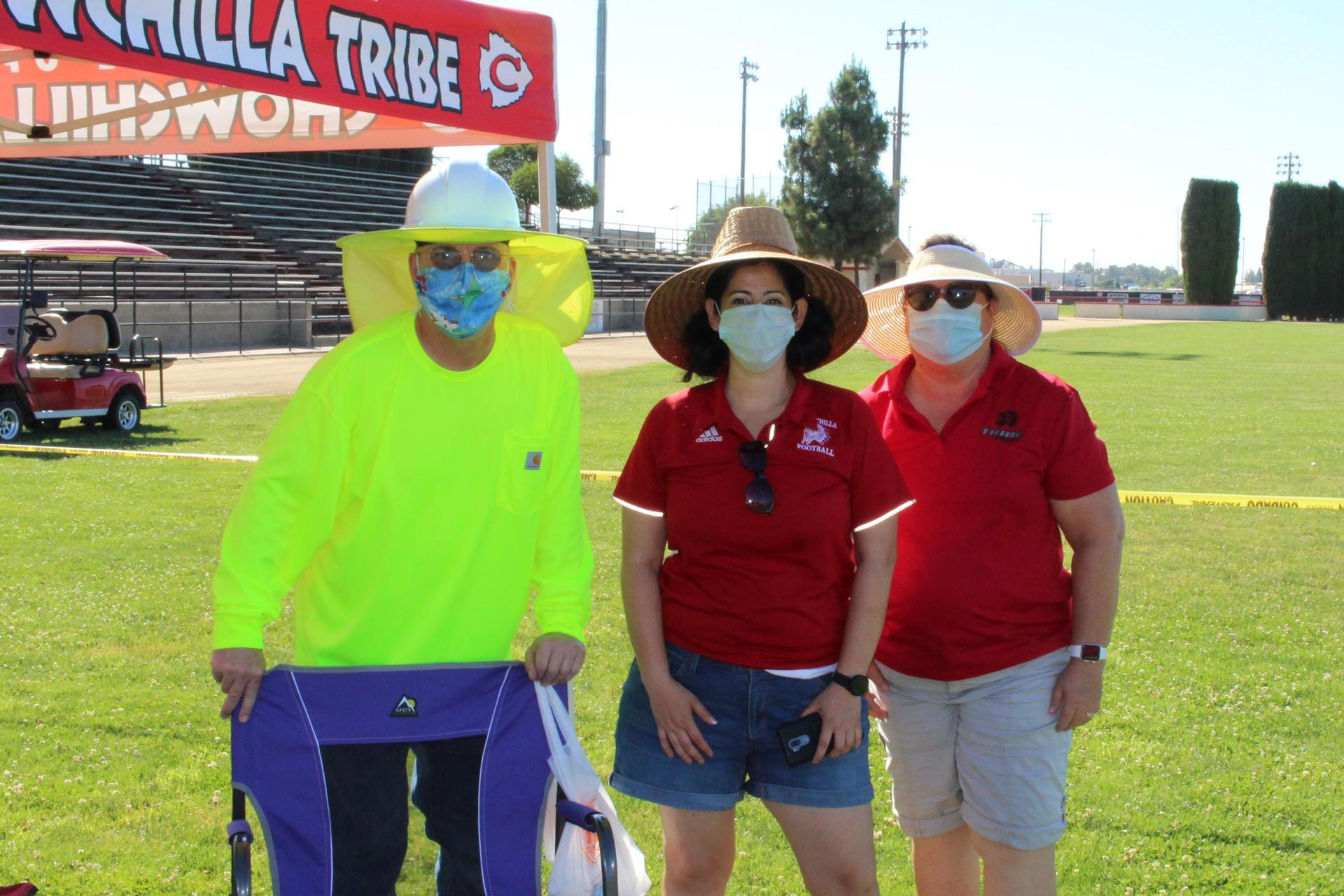 Bob Galloway, Karina Plascencia and Michelle Irwin pose at the tassel station