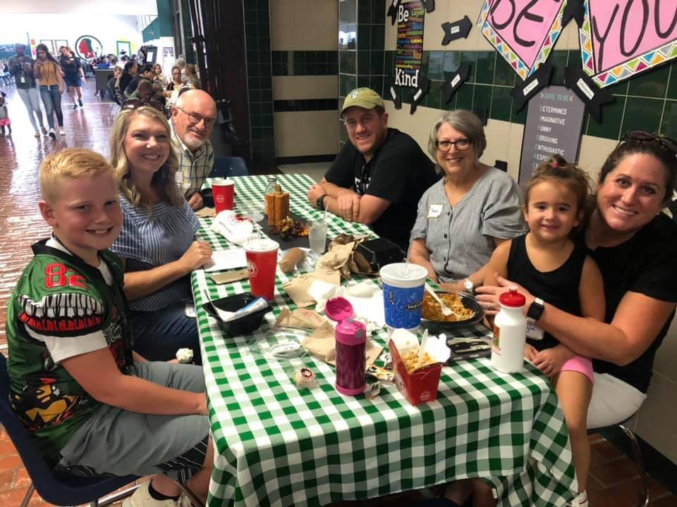 multiple generations pose together around lunch table