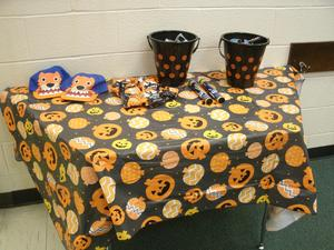 A table with pumpkin and jack-o-lantern tablecloth.