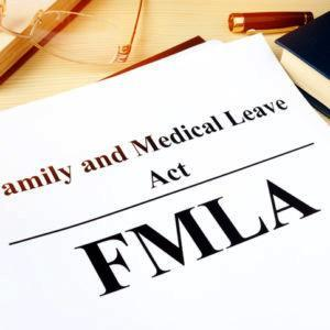 A paper with the letters 'FMLA' across the top, set on a desk with a pair of eyeglasses