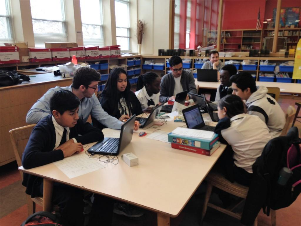 Students and mentors working on computers