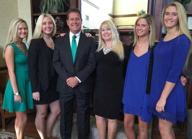 Dr. Bennett standing with his wife and three daughters