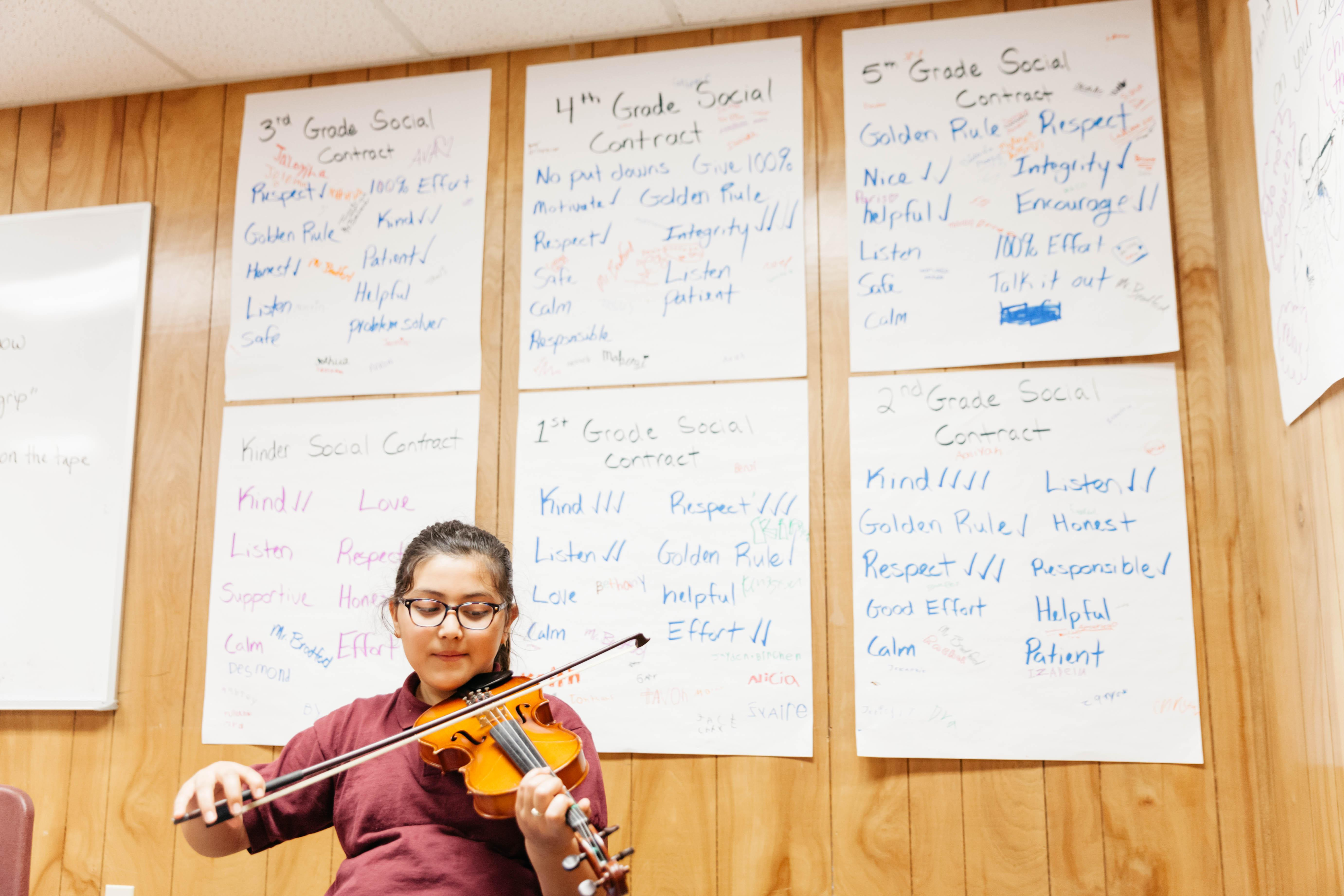 Student playing violin in front of the social contracts.
