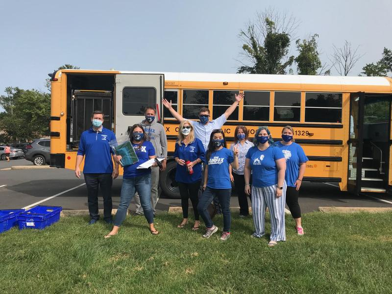 photo of teachers in front of a bus going to meet students in the community