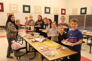 A group of kids at Dix Street assemble plates of cookies.