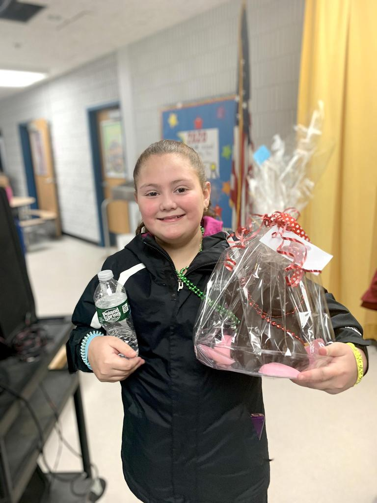 A student holds a large gift basket