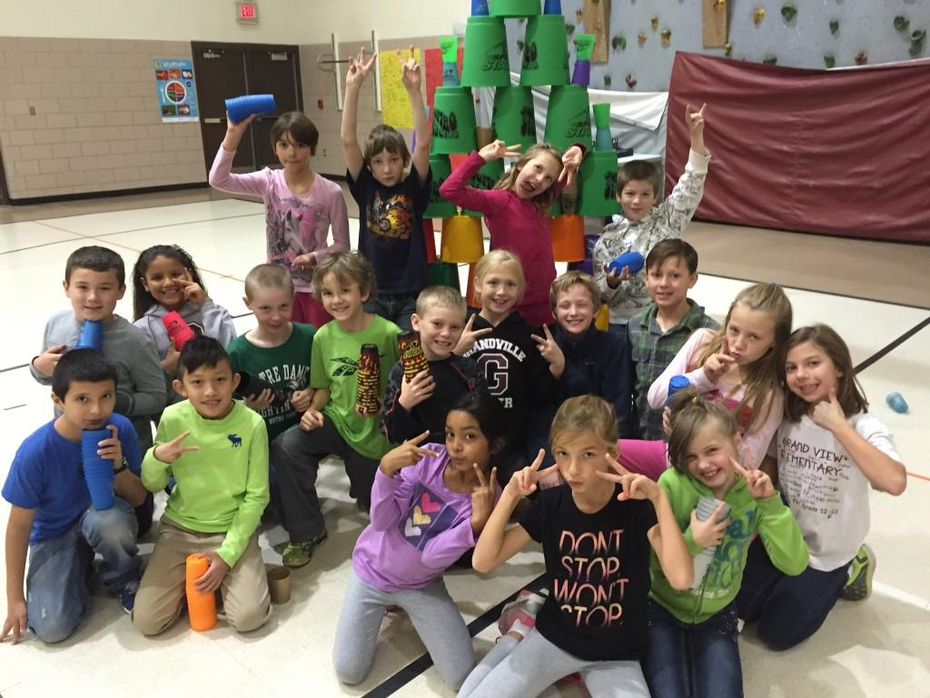 students pose with cups and pails in gym