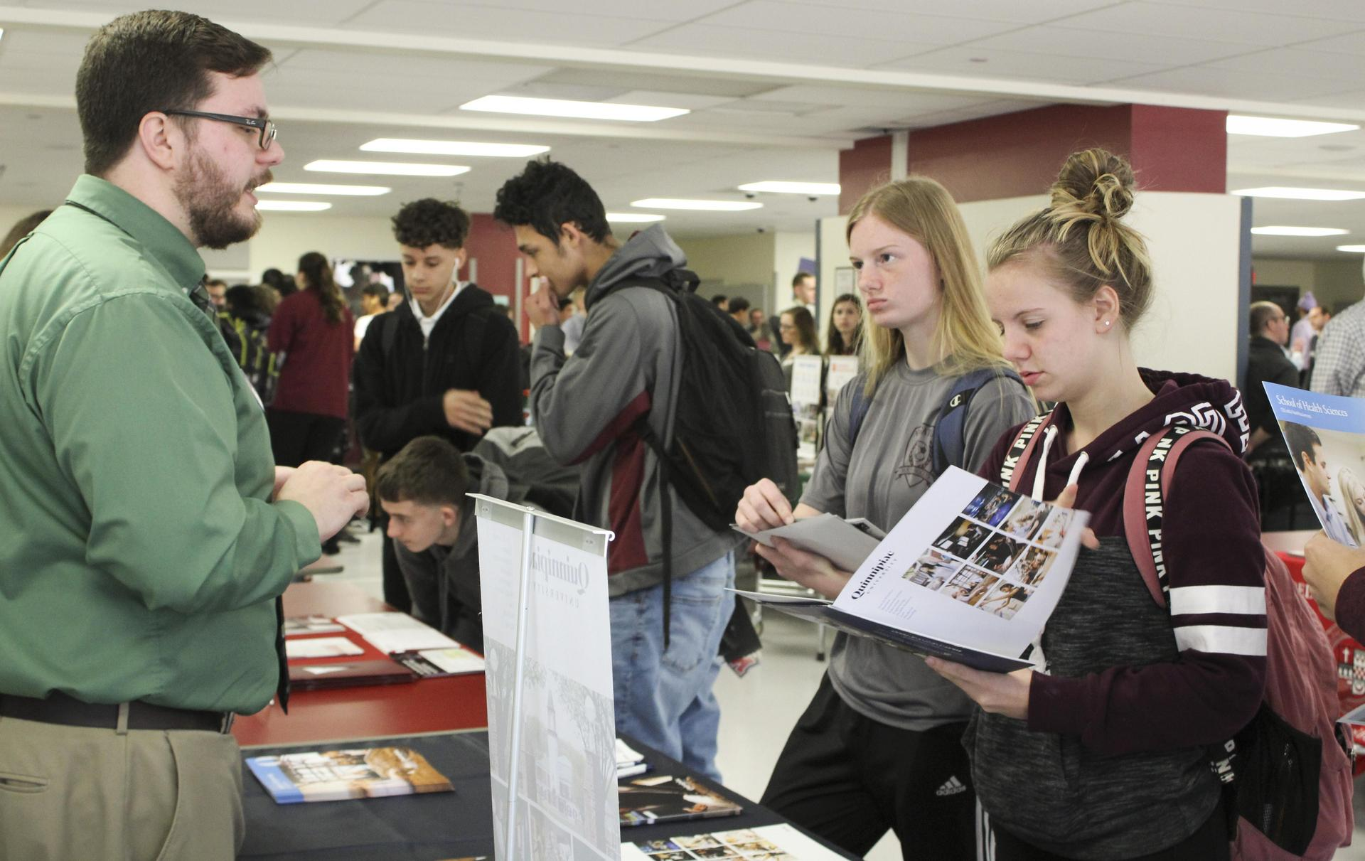 Students talk to college admissions staff during the college fair