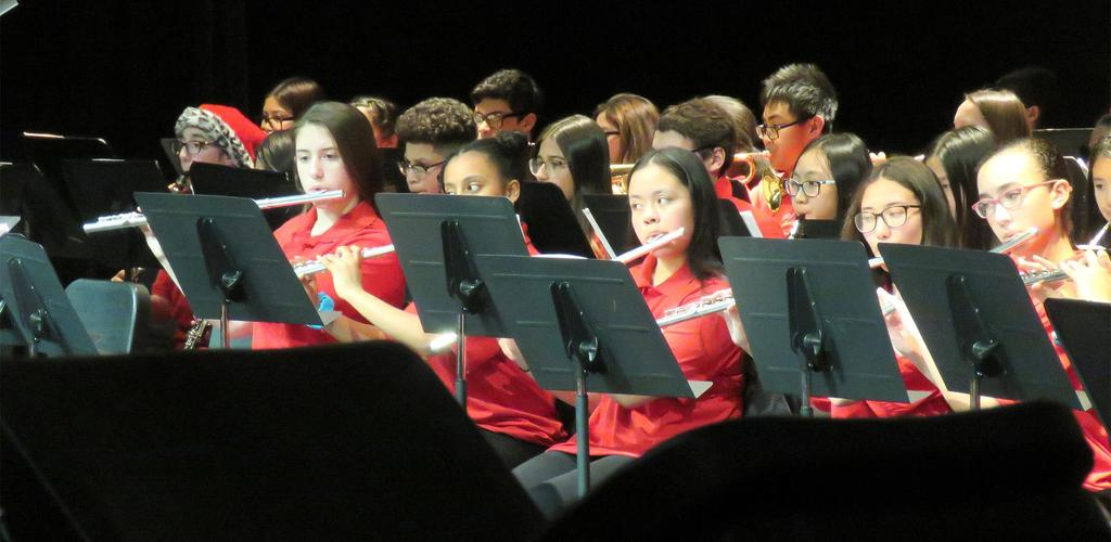 A close-up of a section of the middle school band, featuring a row of flute players