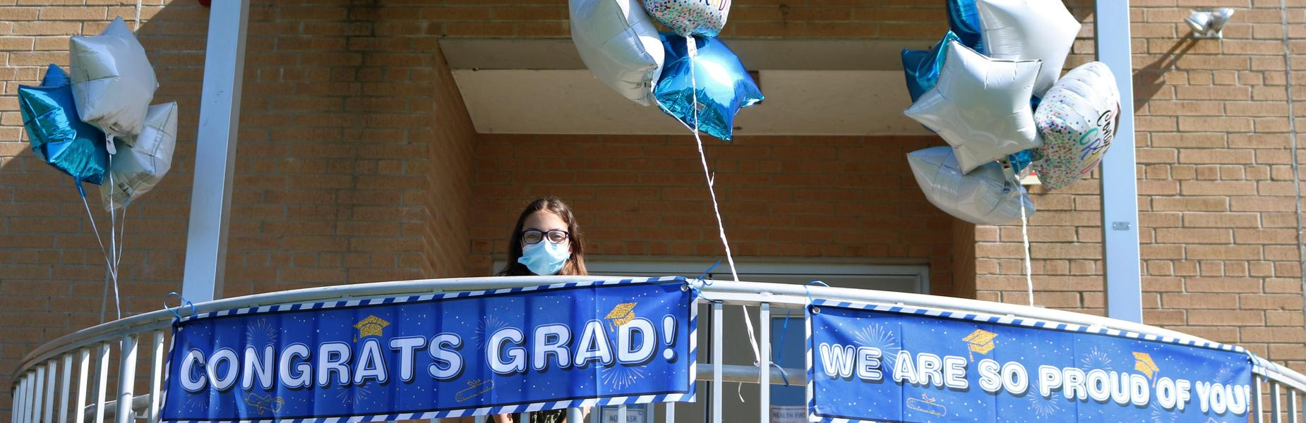 Photo of 5th grader standing next to congratulations signs and balloons on moving up day.