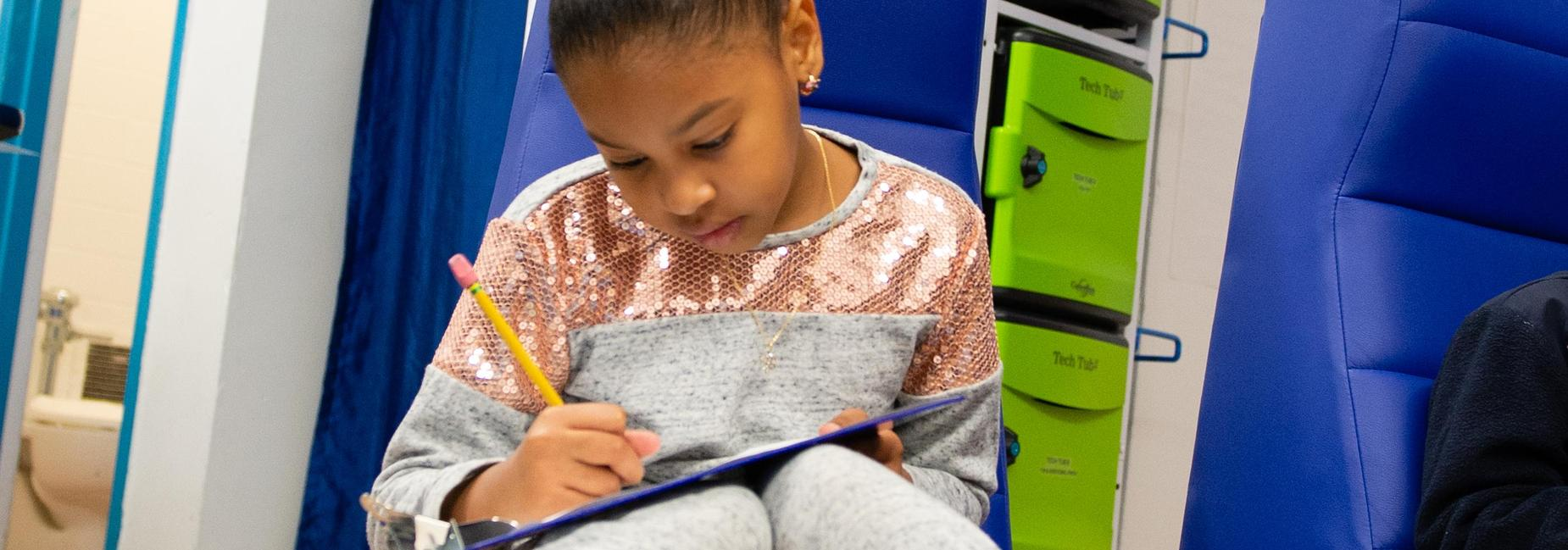 A seated elementary school student writing on a paper on her lap.
