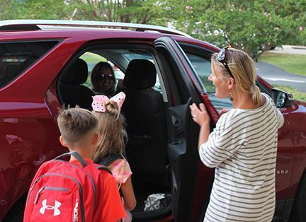 Faculty members and safety patrol members help students into cars during afternoon carpool.