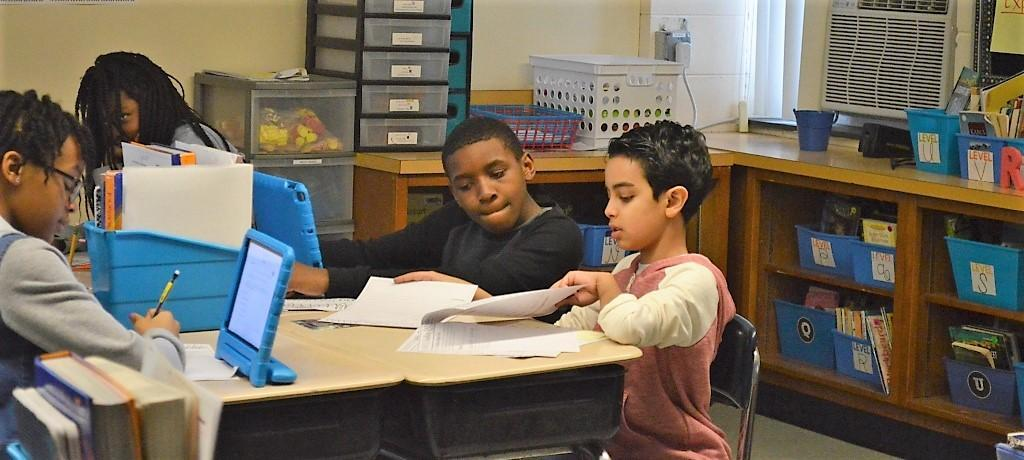 boys collaborating on writing project