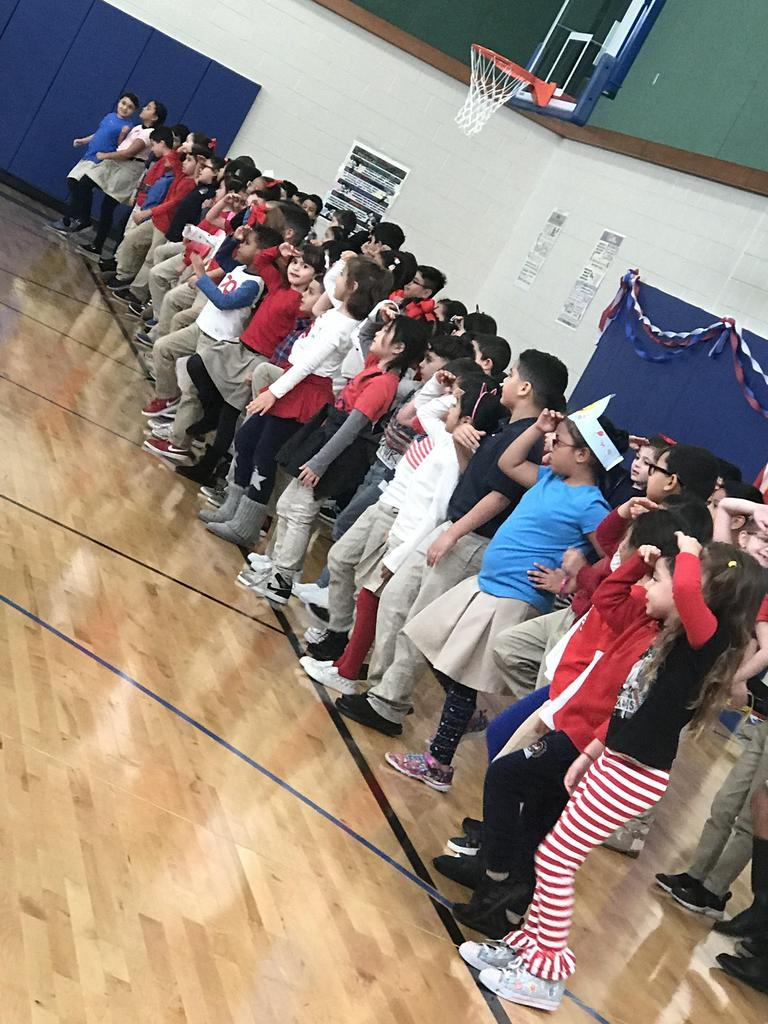 children from grades 1-3 together waving a salute while singing