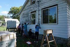 students scraping house in Brightmoor district