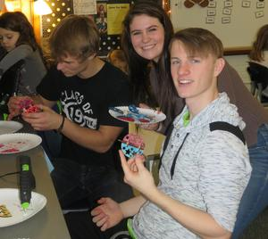 Hunter Allen, Samantha Stayton and Jake Flikkema hot glue the ornaments together.