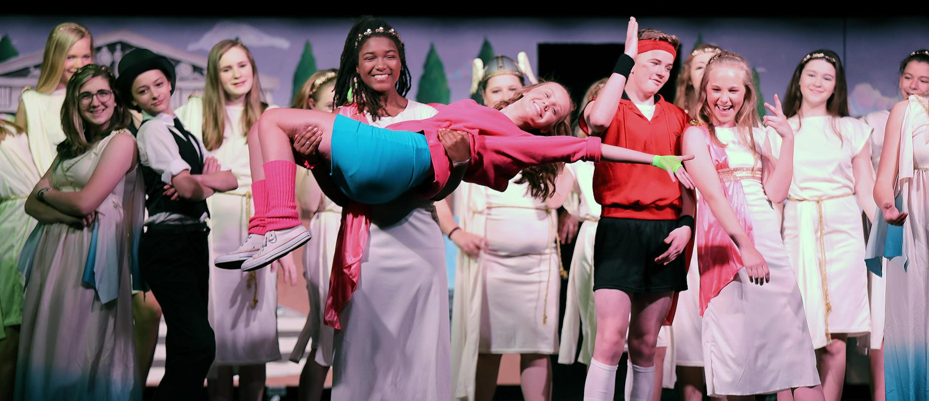 students portray Xanadu Jr. on stage with girl holding onto girl in pink top while rest of cast smiles and celebrates the play