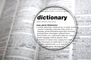 A dictionary page with a magnifying glass highlighting the word 'Dictionary'