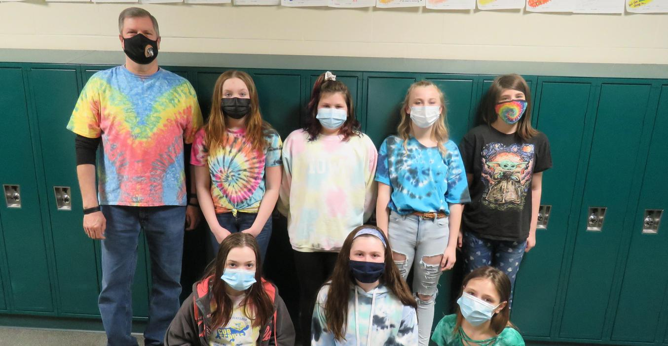 Students and a teacher show off their tie dye fashions during a special week at school.