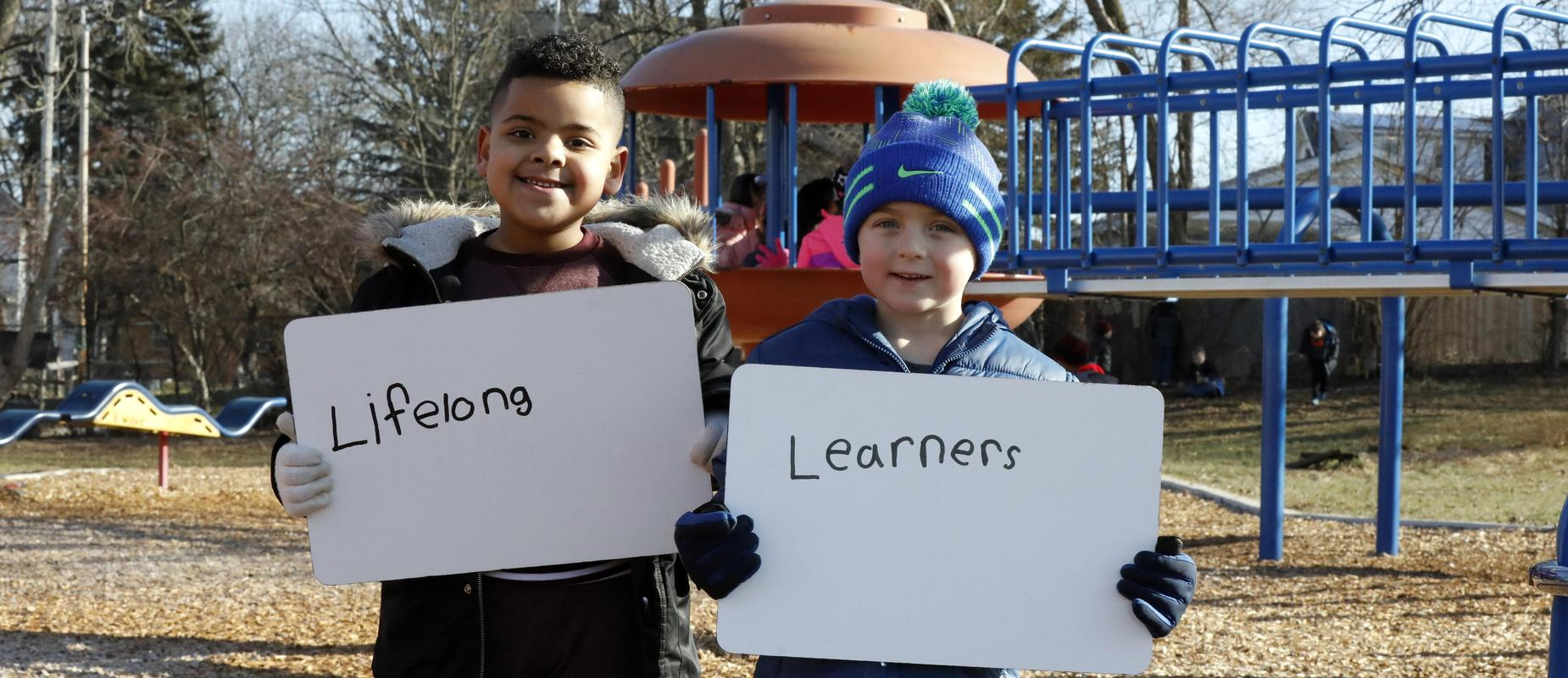 boys pose with lifelong learners sign on playground in their winter gloves and hats and coats