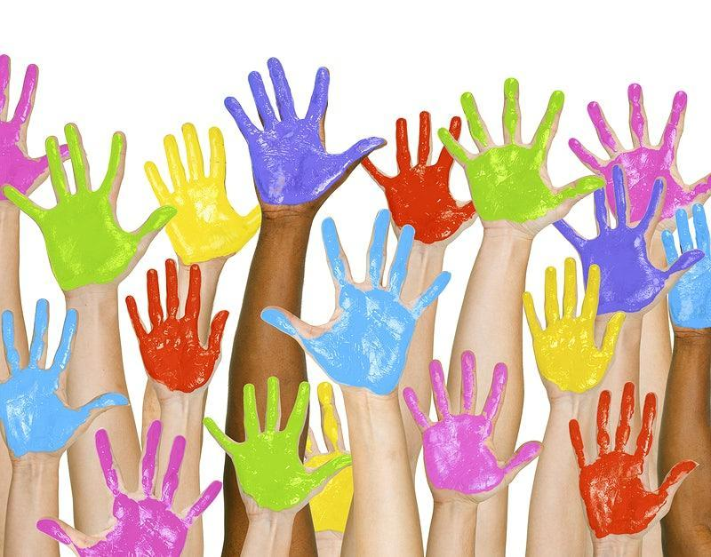 hands raised in the air with colorful paint