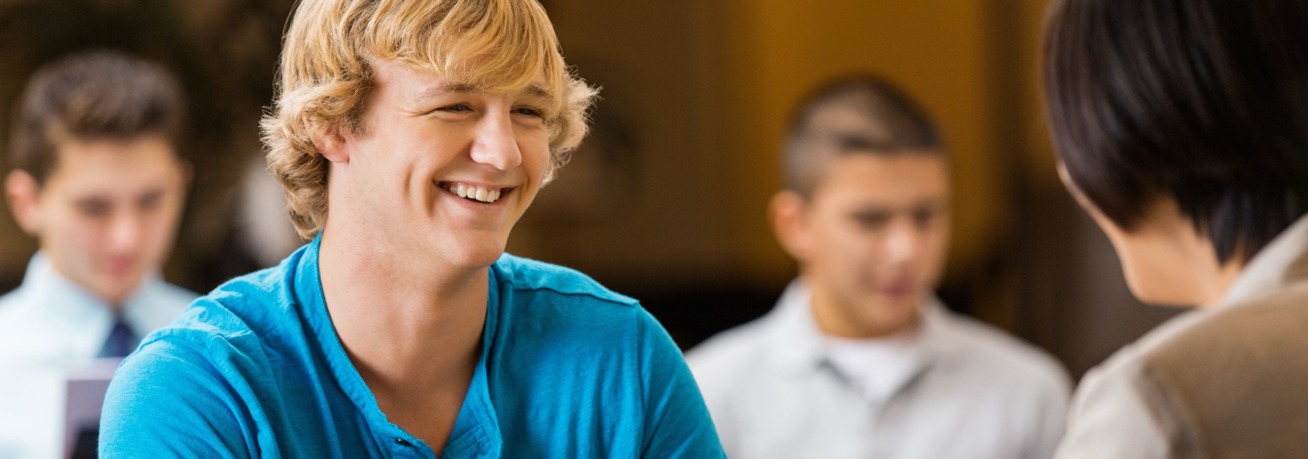 teen boy smiling at woman with her back to the camera