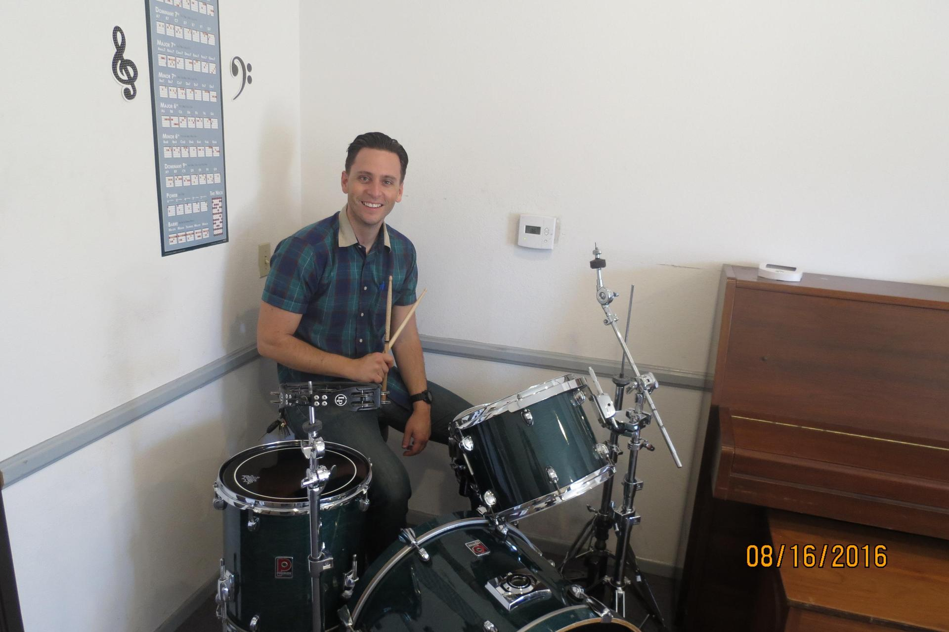 Music teacher, Mr. Ryan, playing drums in his office