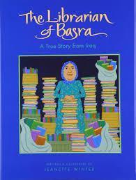 woman with hijab standing among stacks of books
