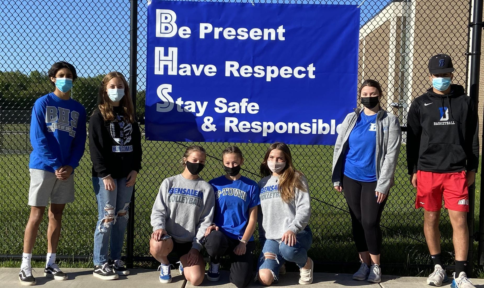 8 girls and boys wearing Bensalem gear in blue, gray, and black standing next to a sign that says BHS: Be Present, Have Respect, Stay Safe and Responsible