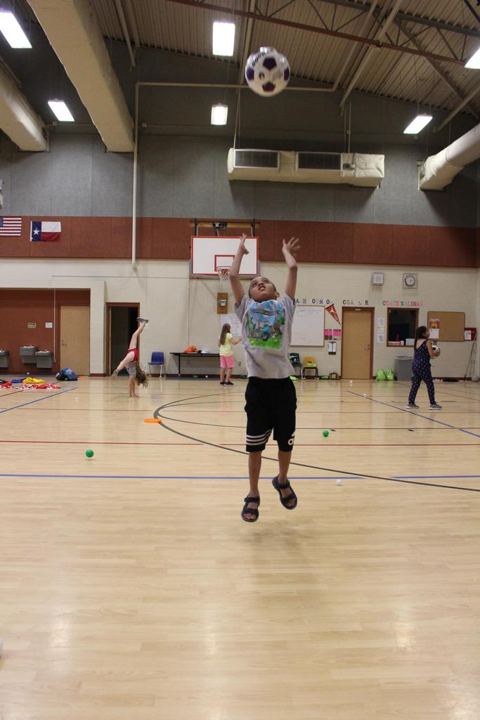 All In! Good Sam camper, Raiden Guerra shoots a soccer ball into the basketball hoop at the Jacob's Well Elementary School Gymnasium.