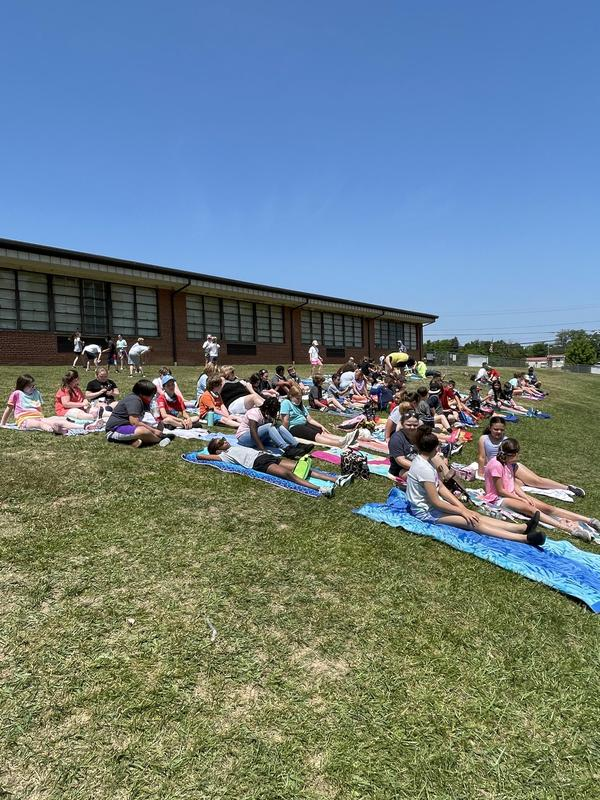 Students sitting on towels on the hill during Field Day.