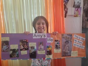 Amy holding her life poster
