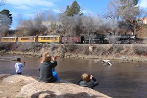 Preschool students waving to the train across the river.