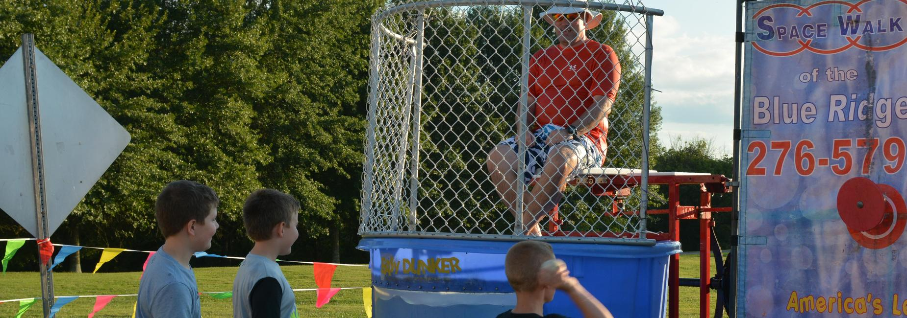 Students take aim to dunk principal in dunking booth.