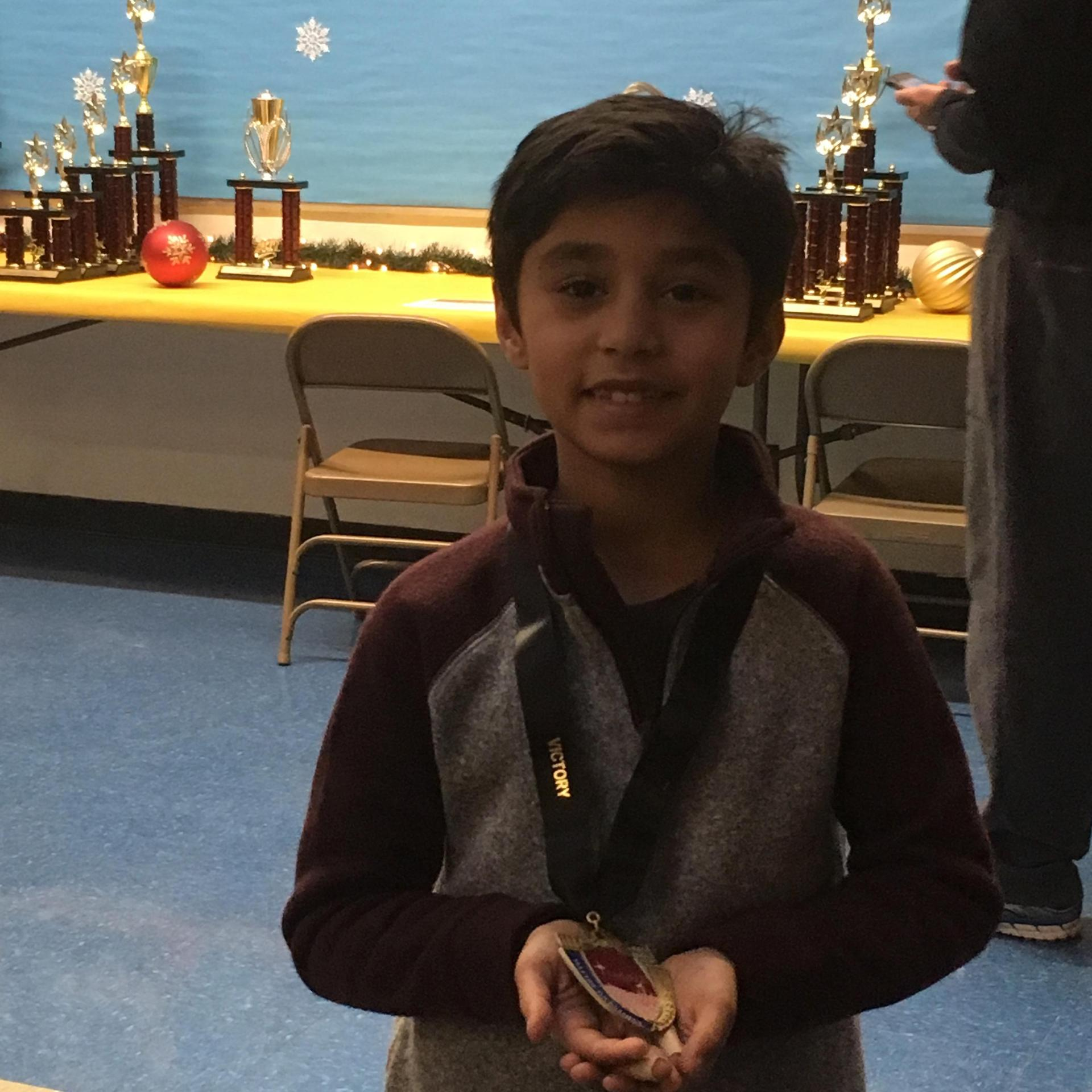 kid smiling with chess medal