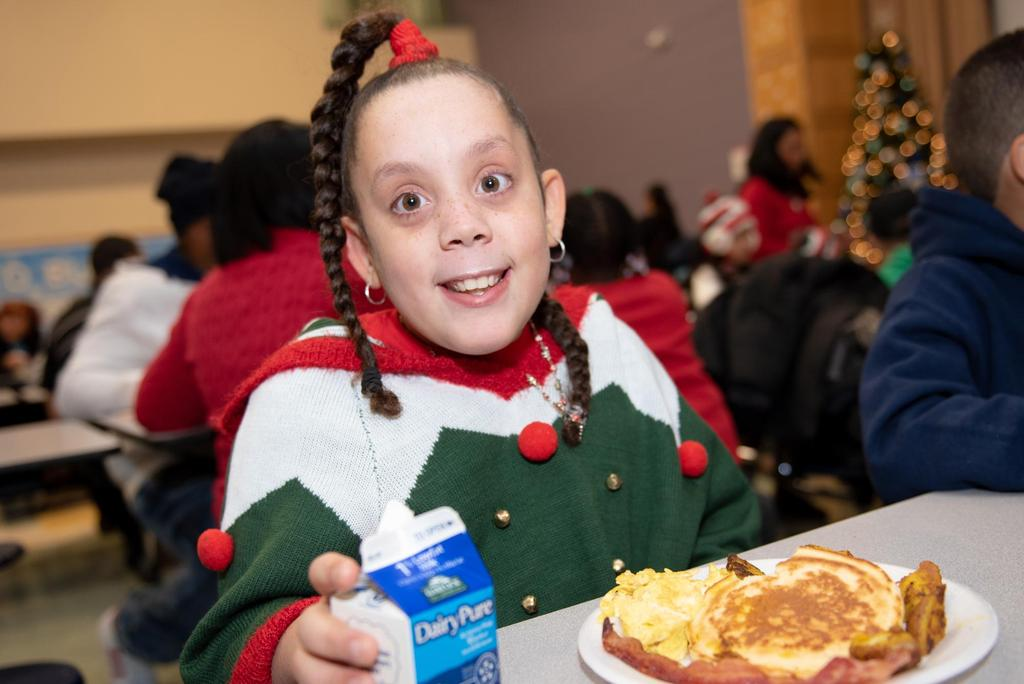 A student wearing a festive holiday sweater in front of a full plate of breakfast food