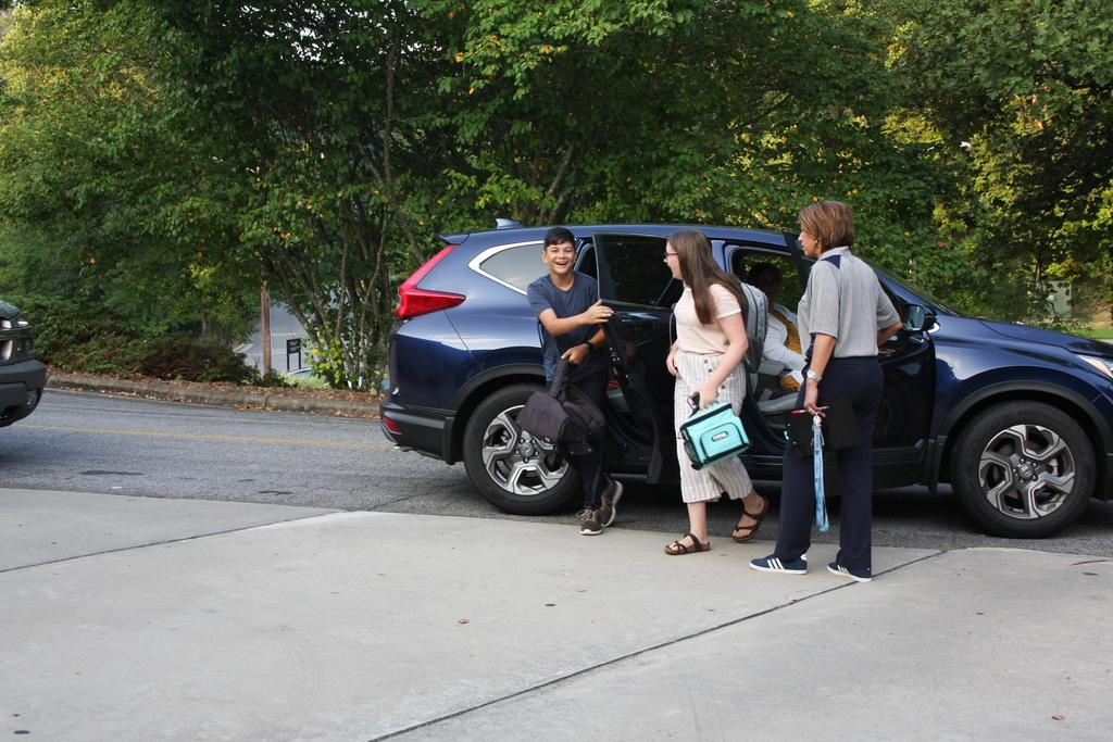 Two student greeted by principal on the first day of school at WECHS as they get out of the car.