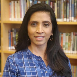 Kavitha posed in front of bookshelf.