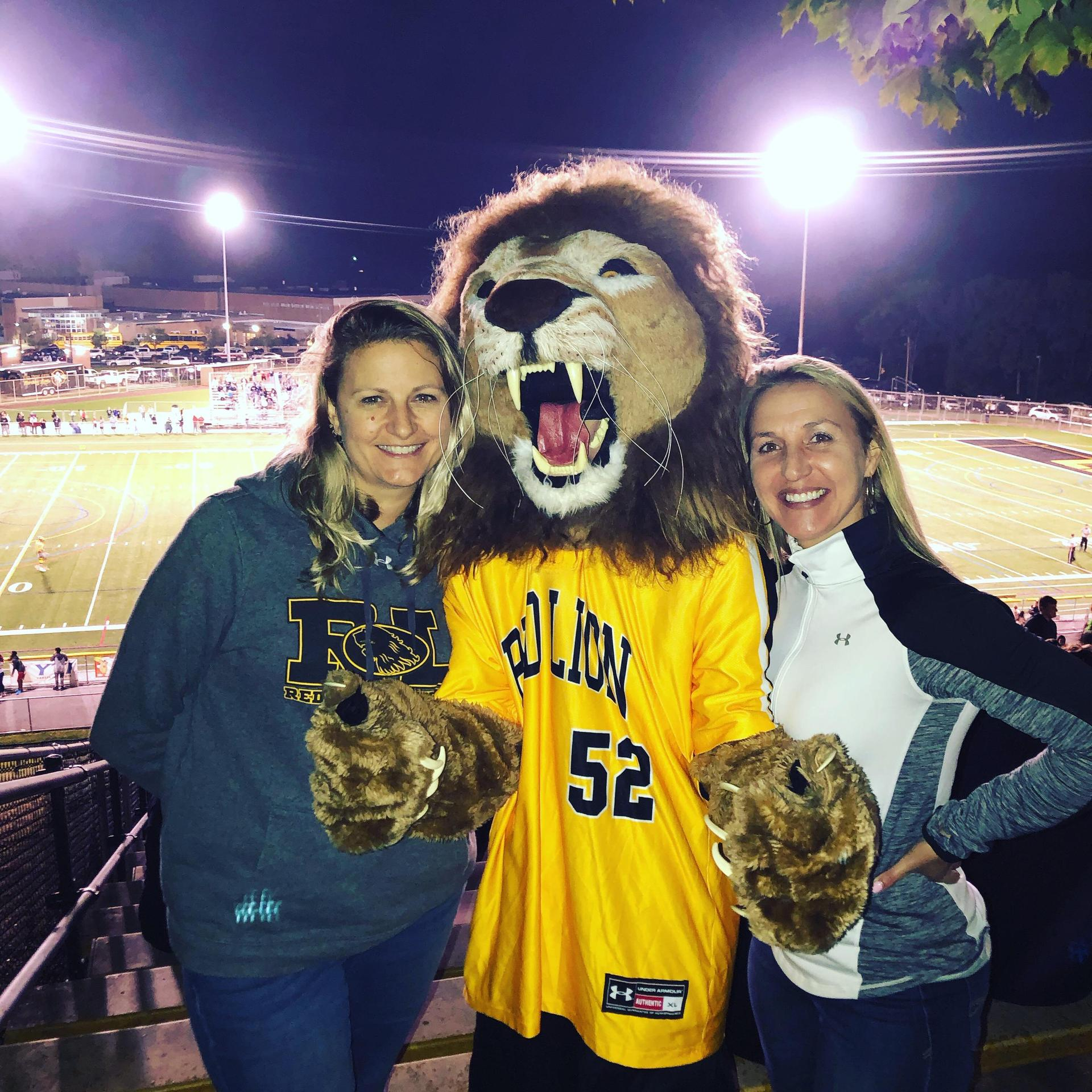 Mrs. Shealer and Mrs. Strausbaugh enjoying a football game with Leo the Lion.