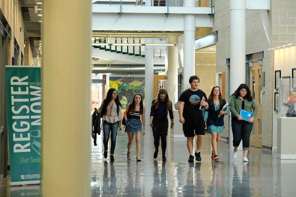 Students walking inside the Levine campus building.