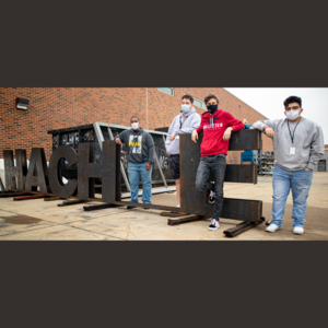 4 teen boys stand among metal letters they welded