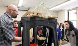 Photo of: Roosevelt Intermediate School science teacher Jeffrey Robbins tests a carefully designed bridge built by students during a semester-long Science Olympiad to see how much weight it can hold.