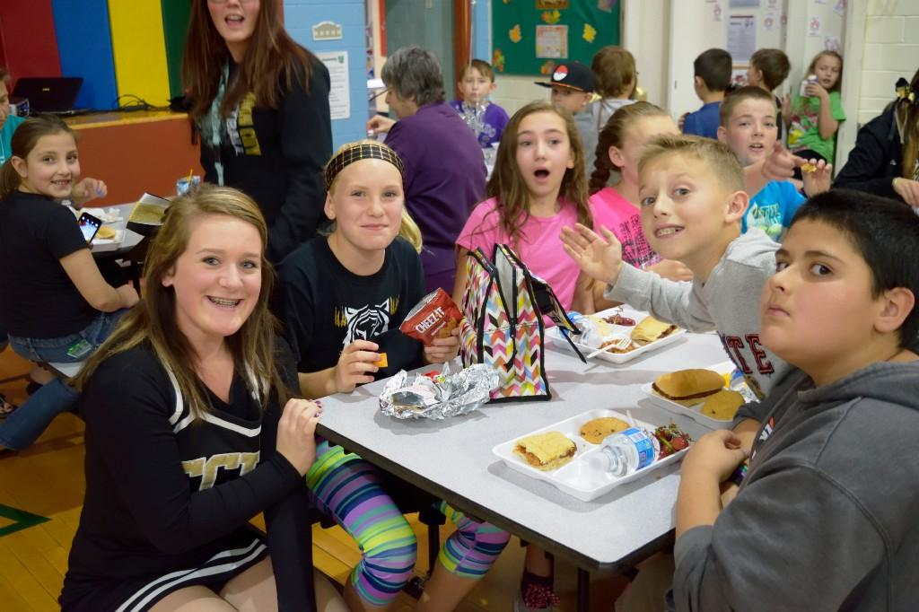 Cheerleaders eating with students