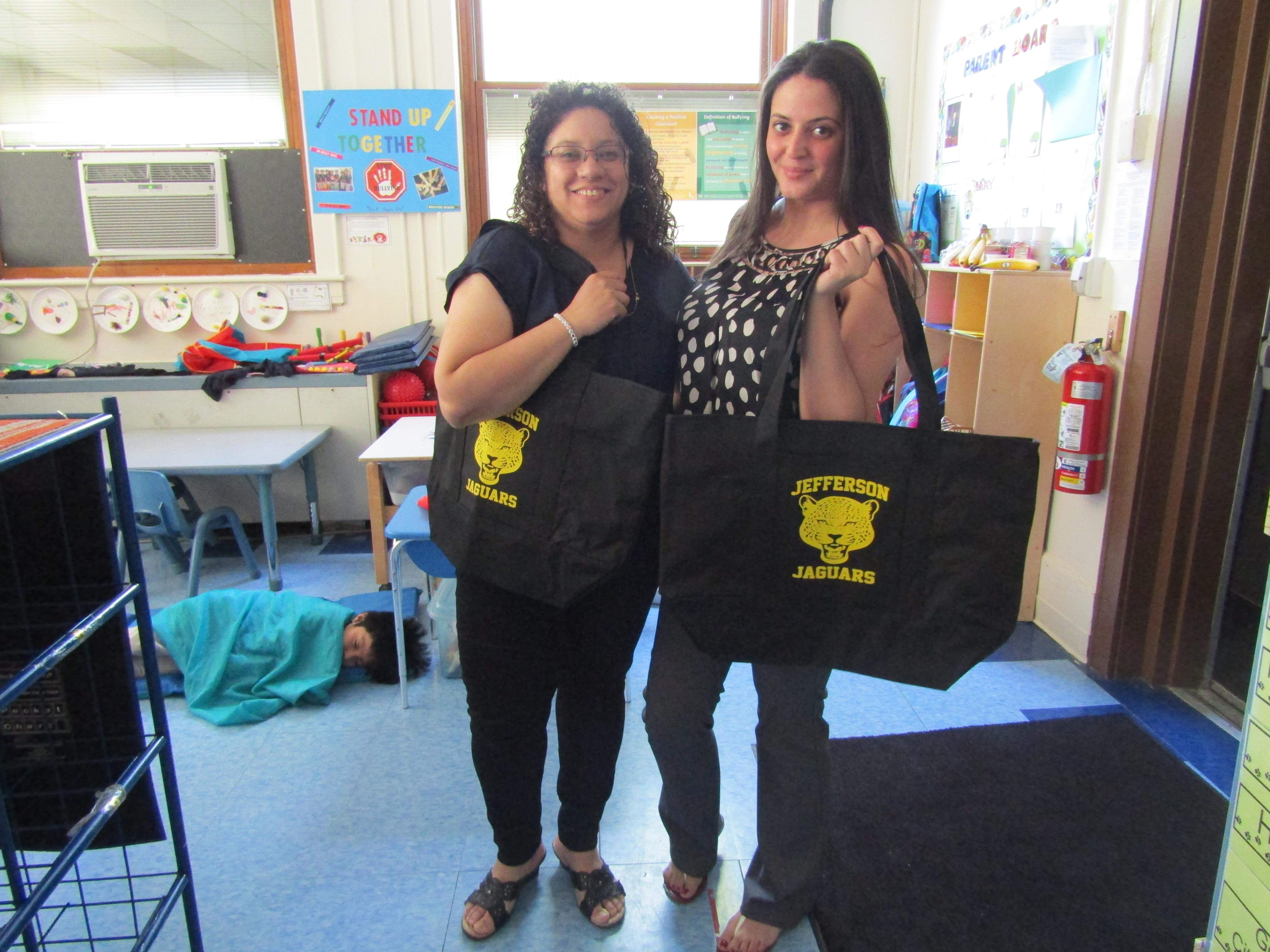 teacher and aide proudly holding their jaguar tote