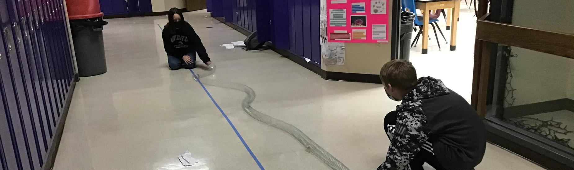 Students working on the floor with a slinky lab