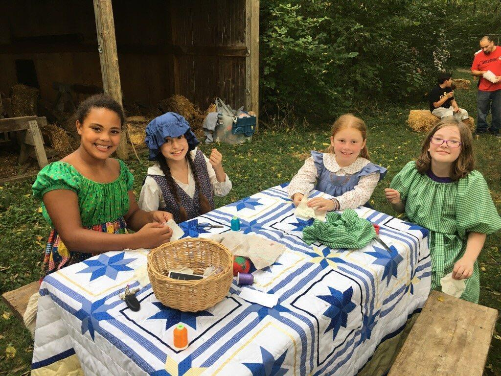 Students dressed as Pioneers sitting at a picnic table with sewing supplies.
