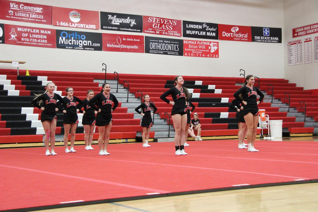 Cheerleaders cheering on a mat in a gymnasium