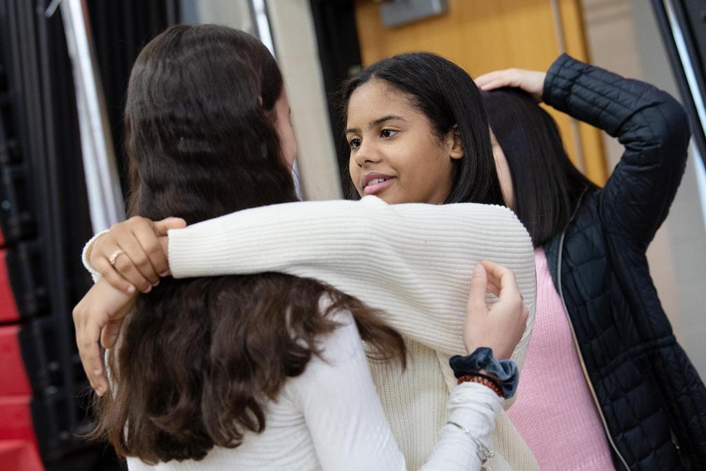 A student embraces a classmate